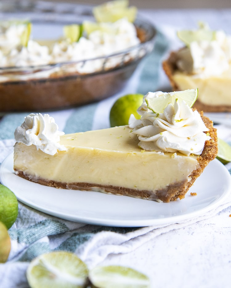 A side shot of slice of key lime pie topped with whipped cream rosettes and small lime slices, all served on a white plate.