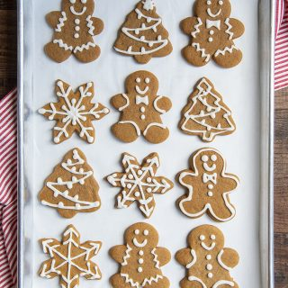 A cookie sheet lined with gingerbread cookies. There are gingerbread men, trees, and snowflakes, decorated with a simple royal icing.