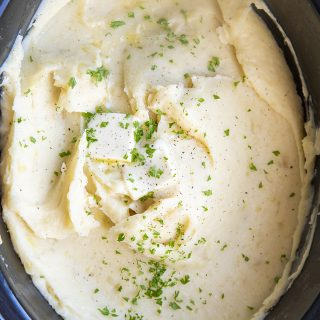 Mashed Potatoes in a slow cooker topped with butter and sprinkled parsley.