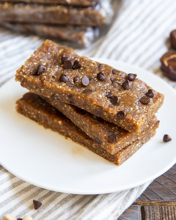 A stack of three copycat peanut butter chocolate chip larabars on a small plate with mini chocolate chips showing on the top one.