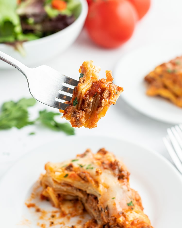 A bite of lasagna on a fork, above a piece of it on the plate.