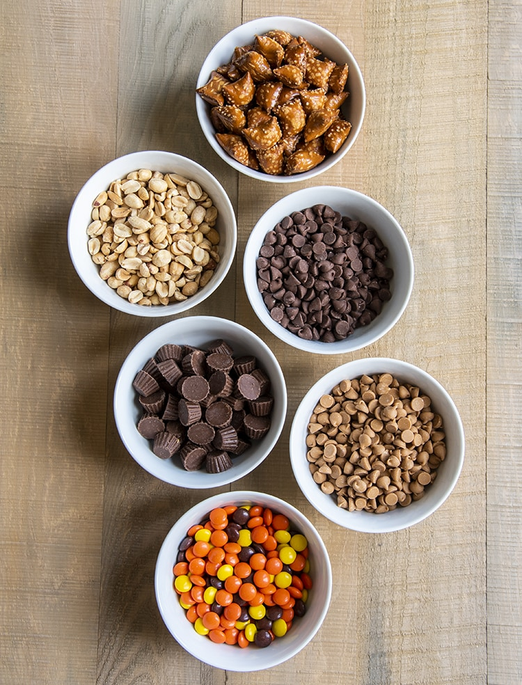 Small bowls of peanut butter filled pretzels, salted peanuts, chocolate chips, mini peanut butter cups, peanut butter baking chips, and reeses pieces.