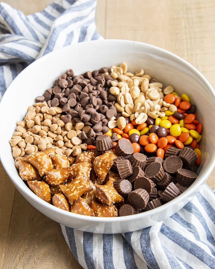 A bowl full of the ingredients for a chocolate peanut butter snack mix, the ingredients are all separated. There are peanuts, then reeses pieces, then mini peanut butter cups, then peanut butter filled pretzels, then peanut butter baking chips, then chocolate chips, starting at the top and going clockwise.
