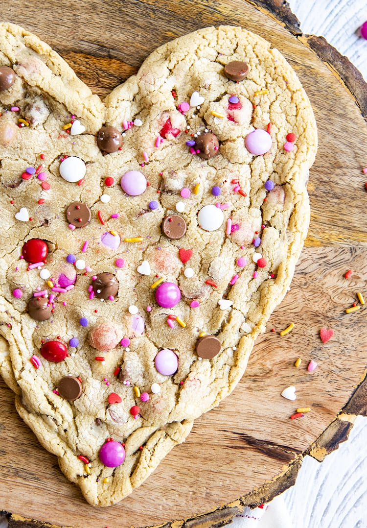 A giant heart shaped cookie on a wooden board. The corner of the cookie isn't in the shot. The cookie is topped with chocolate chips, and valentine pink, red, and white, m&ms.