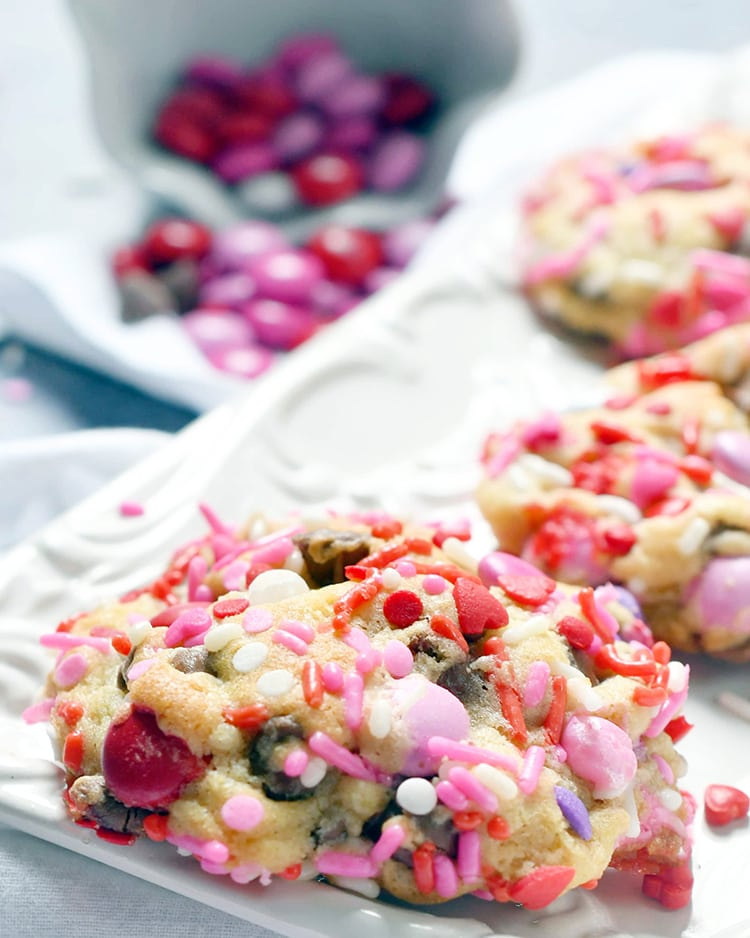 A close up of a valentine m&m cookie covered in valentine colored red and pink sprinkles on a white plate.
