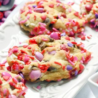 Valentine Sprinkle M&M cookie covered in red, pink, and white sprinkles topped with red, pink, and white M&Ms on a white plate.