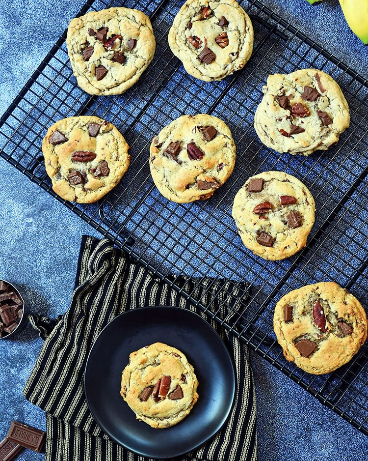 banana chocolate chunk cookies on brown plate and cooling rack on blue background.