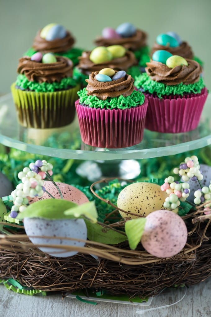 Cupcakes decorated with a green frosting to look like grass, and a brown frosting to look like a nest, and m&ms on top for eggs.
