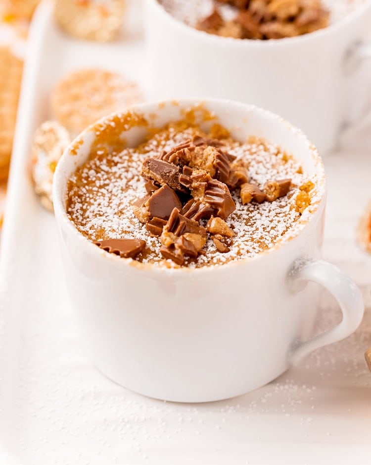 A nutter butter mug cake in a white mug sprinkled with powdered sugar, and topped with chopped peanut butter cups.