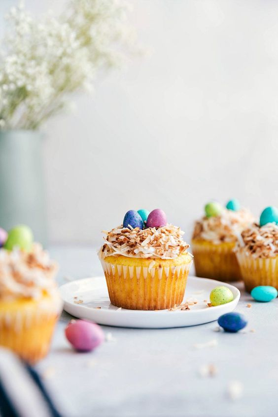 A yellow cupcake on a plate topped with white frosting, and toasted coconut to look like a birds nest, then three chocolate candies on top to look like eggs.