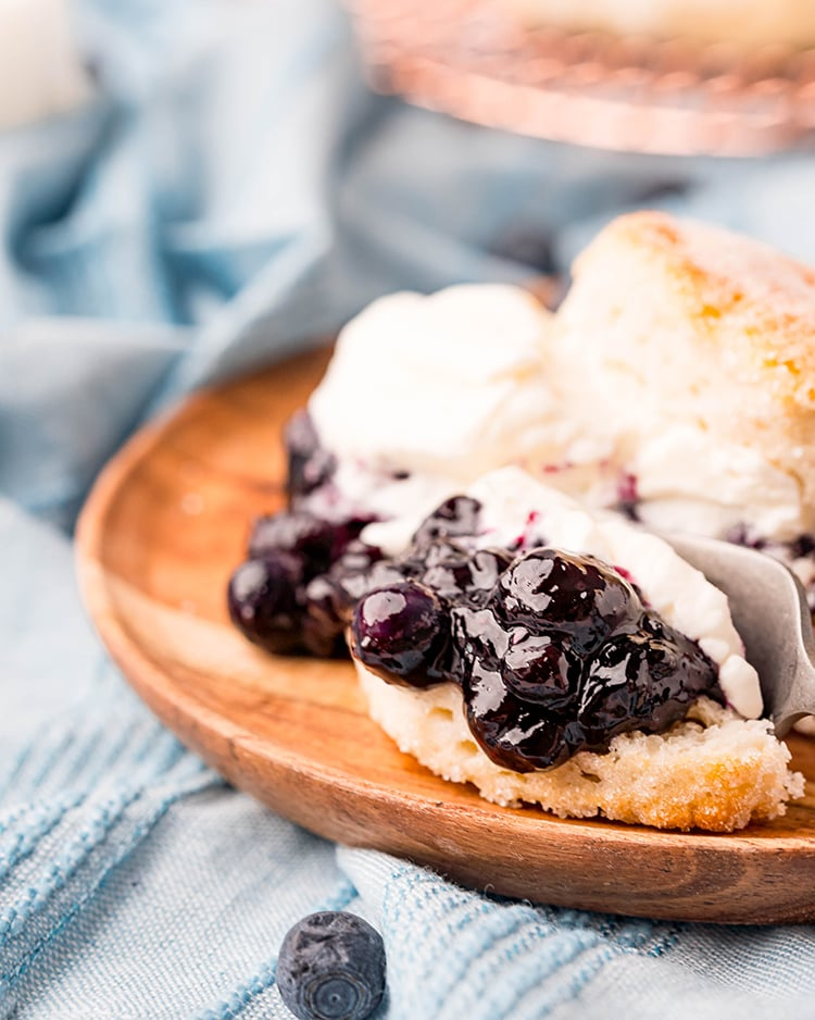 A close up of a blueberry shortcake on a wooden plate, with a fork cutting into it.