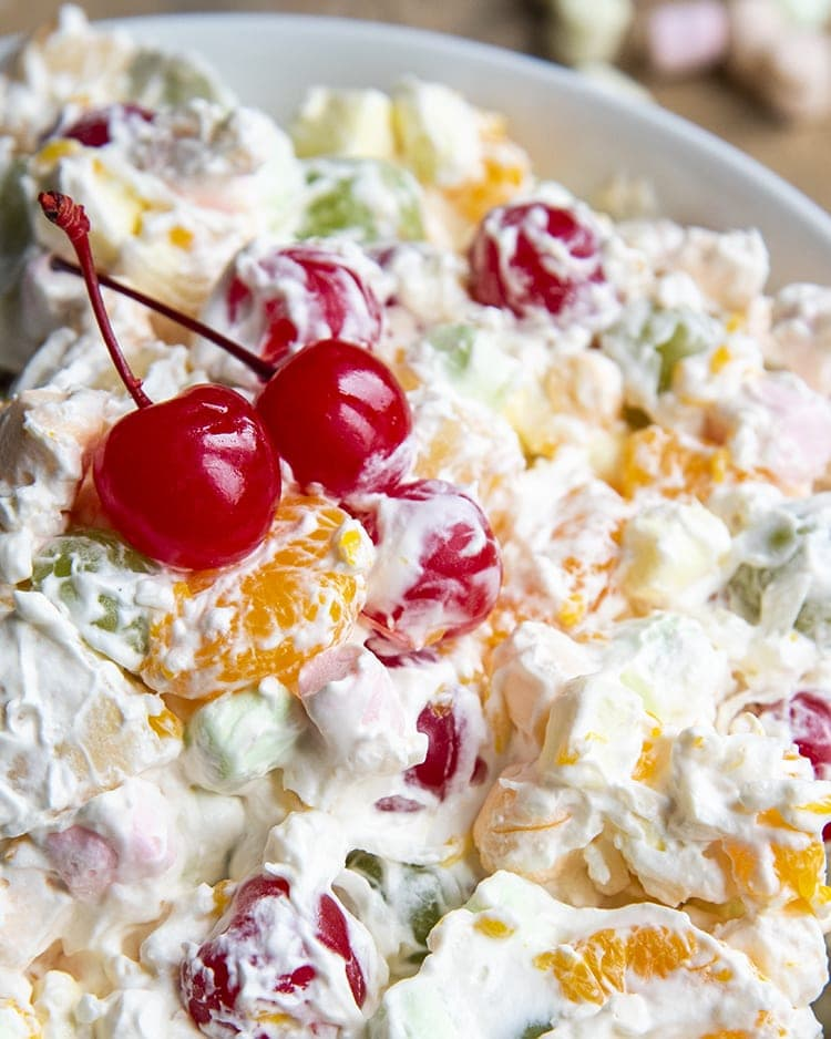 A close up of a bowl of fruit salad covered in a creamy sauce. Topped with two red maraschino cherries.