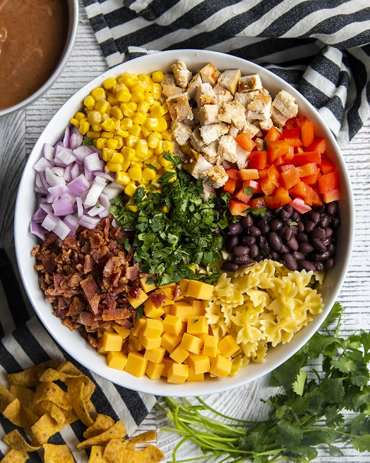 A bowl of the ingredients needed for bbq ranch pasta salad. There is farfalle noodles, black beans, red bell pepper, chopped chicken, corn, red onion, bacon, cheese cubes, and cilantro in the middle.