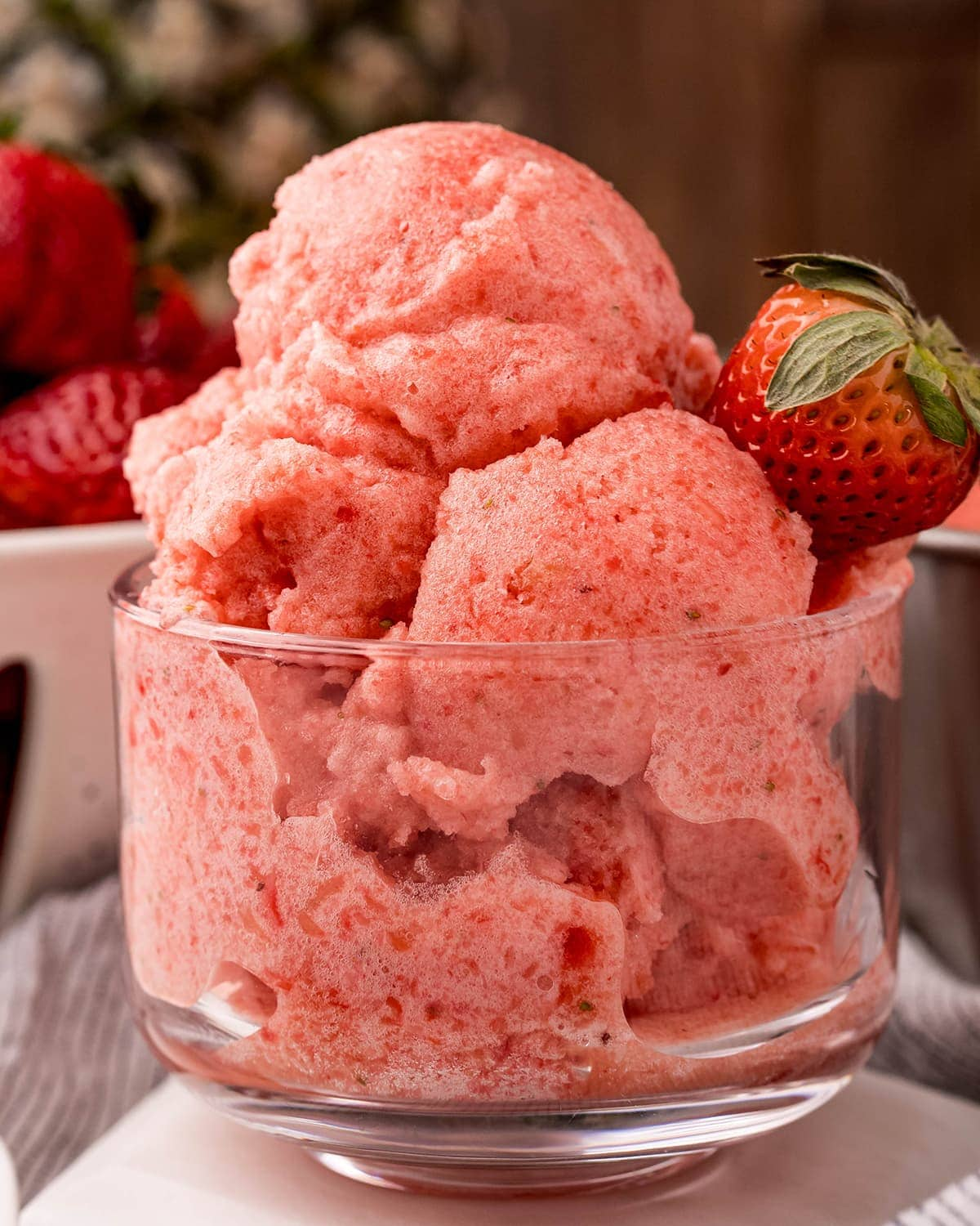 A clear glass bowl piled high with a pink strawberry pineapple sorbet, topped with a fresh strawberry.