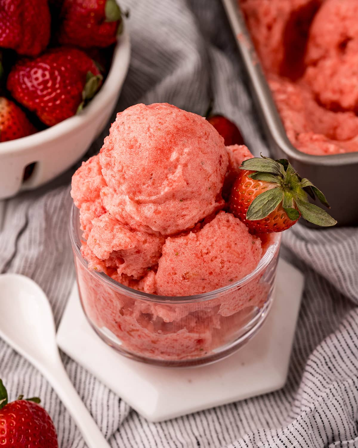 A clear glass bowl piled high with a pink strawberry sorbet, topped with a fresh strawberry.