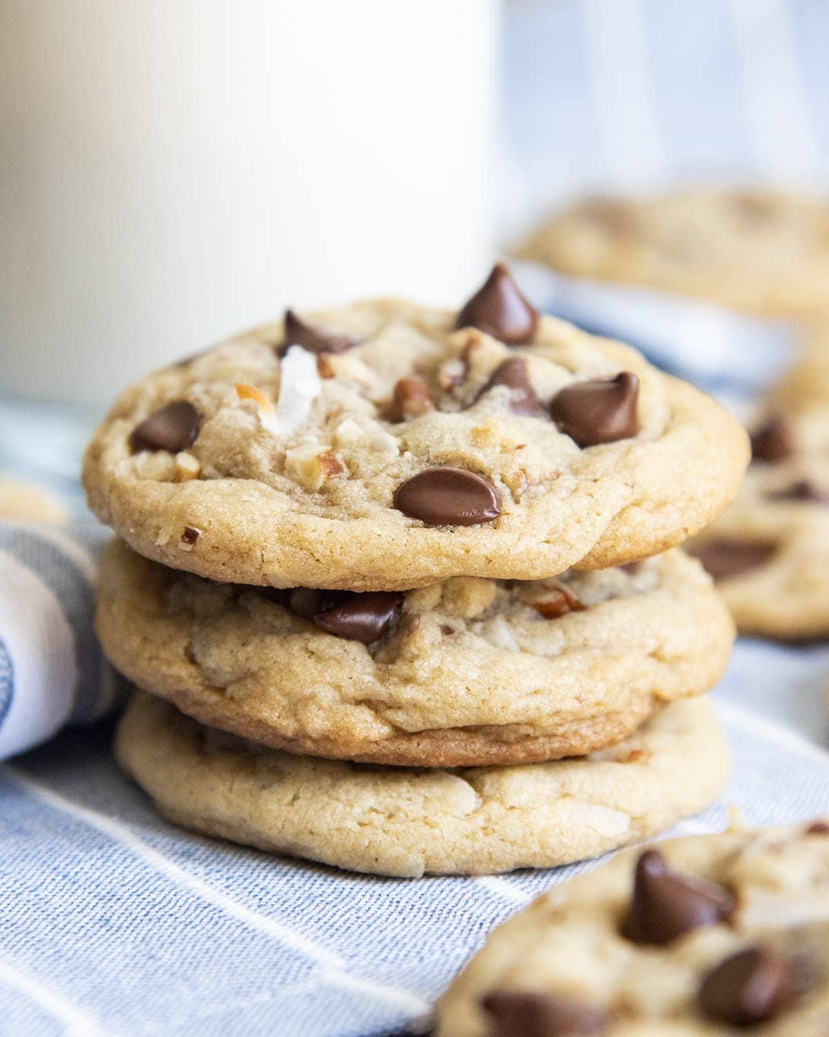 A stack of 3 drop style cookies with chocolate chips, pecans, and shredded coconut.