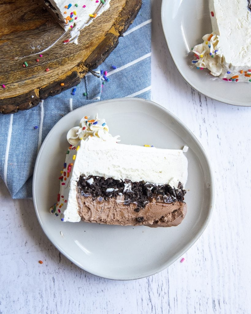 A piece of ice cream cake on a plate, with a layer of chocolate ice cream, cookie crumbs, and vanilla ice cream.
