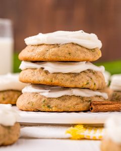 A stack of three zucchini cookies topped with cream cheese frosting.