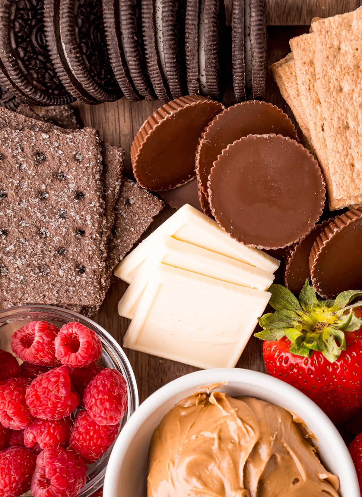 A s'mores dessert board with Oreos, white chocolate squares, Reeses, Raspberries, graham crackers, and peanut butter.