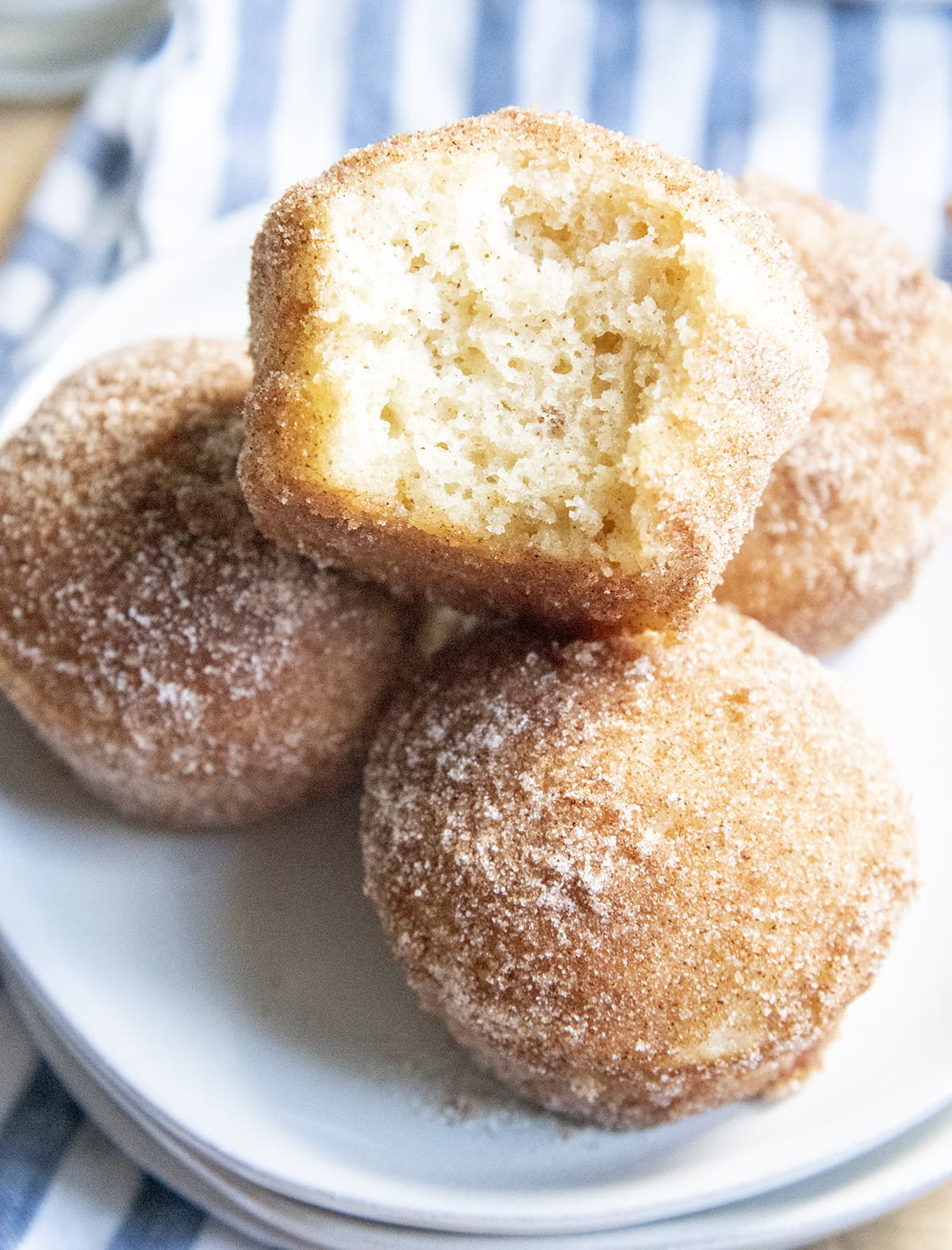 A pile of muffins coated in cinnamon sugar, the top muffin has a bite out of it showing the middle of the muffin.
