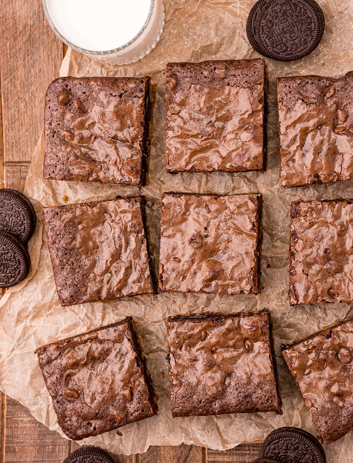 An overhead photo of brownie squares on brown parchment paper.