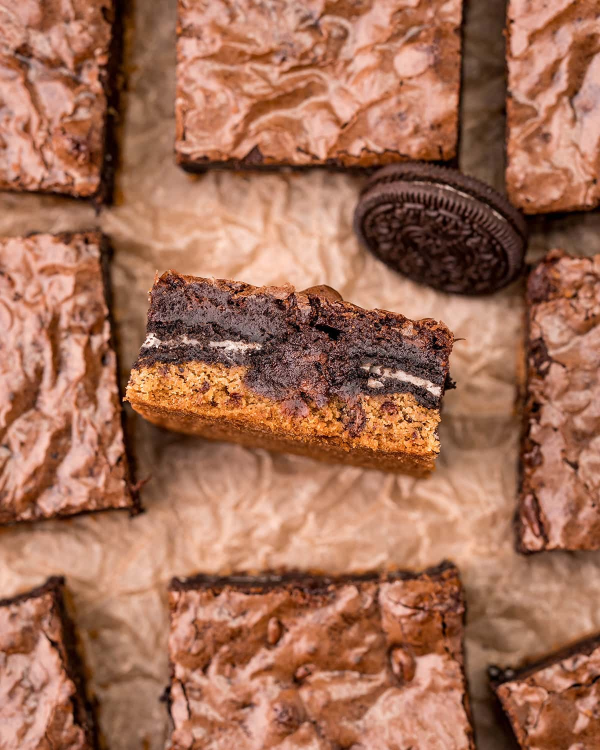 A slutty brownie brookie on its side, with a layer of chocolate chip cookie, Oreos, and brownie.