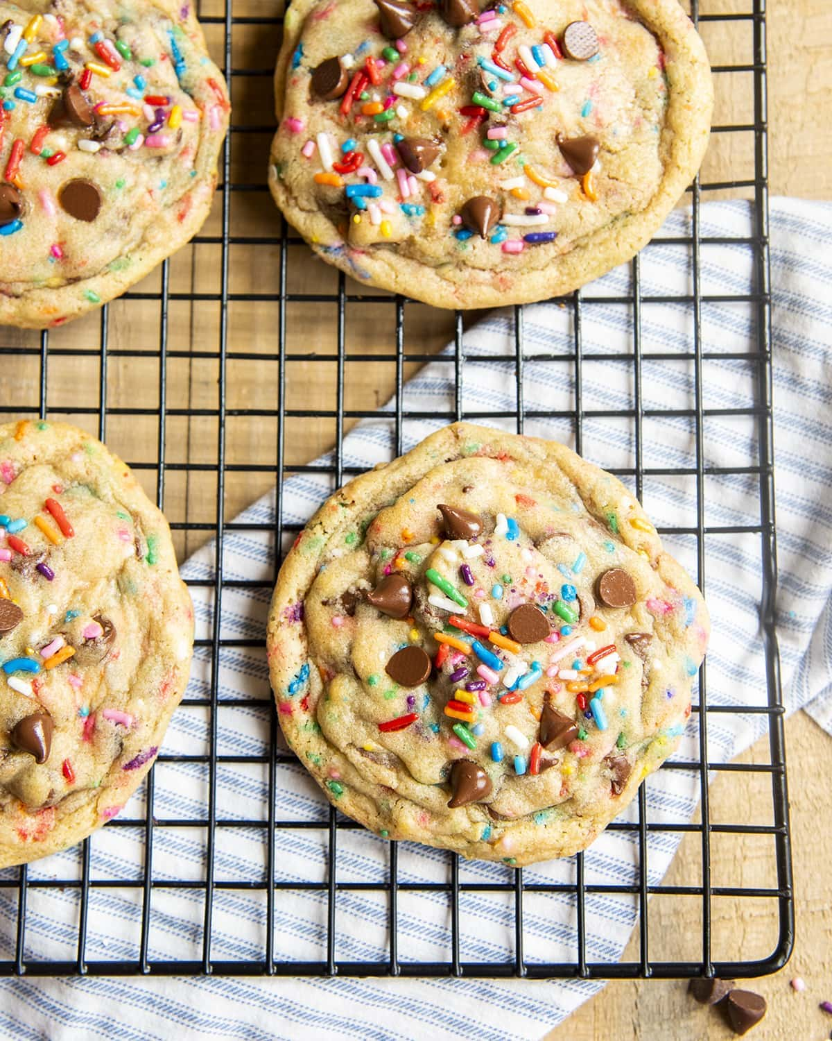 A close up of giant sprinkle and chocolate chip cookies on a cooling rack!