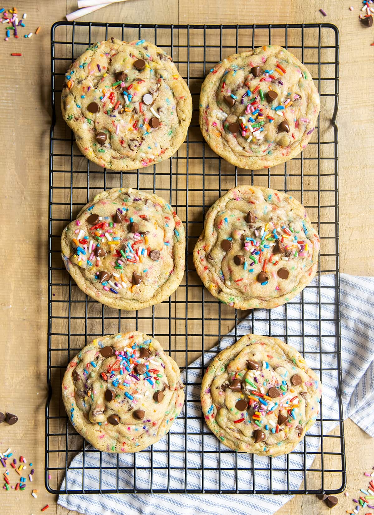 An overhead photo of 6 giant chocolate chip funfetti cookies on a cooling rack.