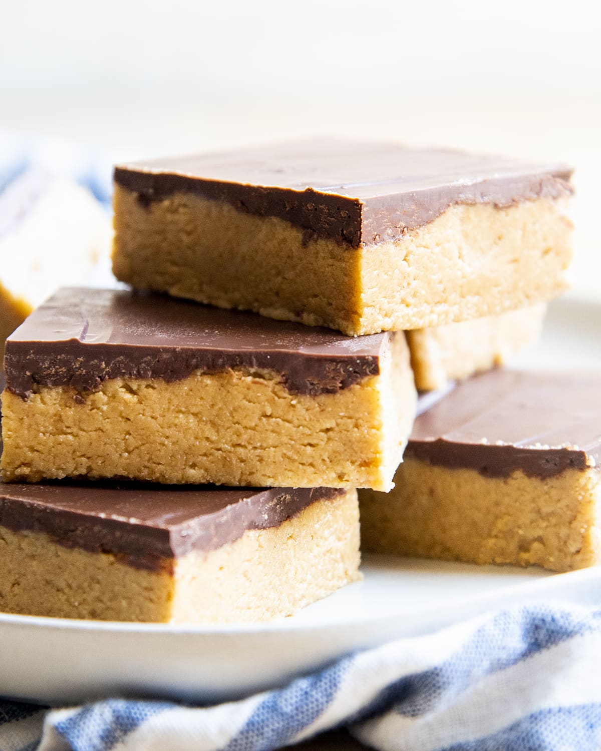 A pile of chocolate peanut butter bars on a plate.