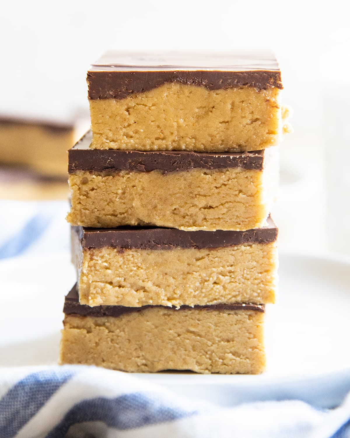 A stack of 4 no bake peanut butter bars topped with a layer of chocolate each.