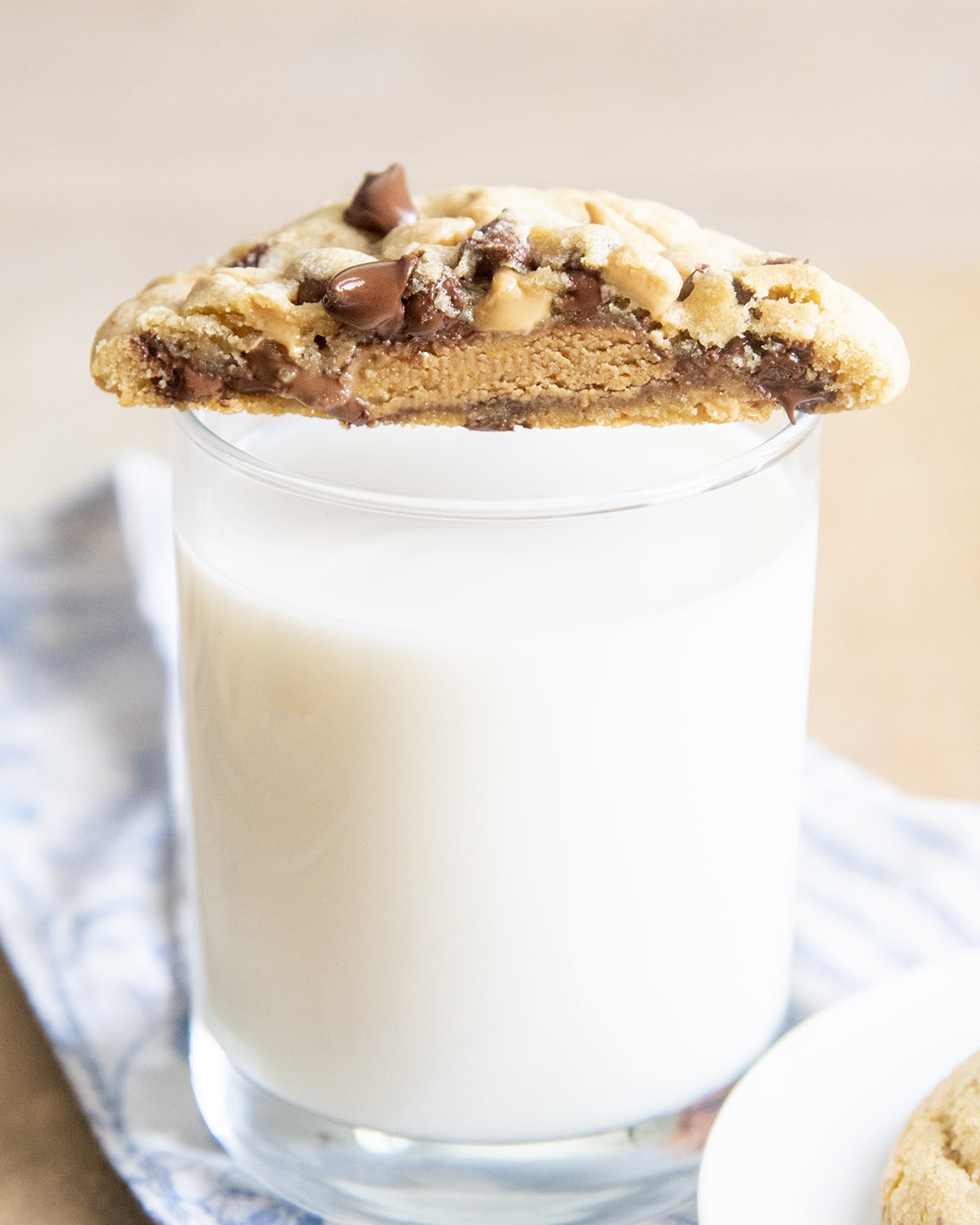 Half a cookie set on a cup of glass, showing the inside of the cookie with a peanut butter cup, and melted chocolate chips.