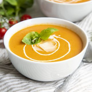 A bowl of roasted tomato soup topped with swirls of heavy cream, and fresh basil leaves.