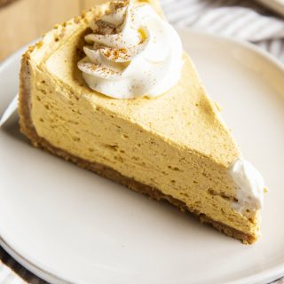 A slice of no bake pumpkin cheesecake, topped with a dollop of whipped cream and a sprinkle of cinnamon.