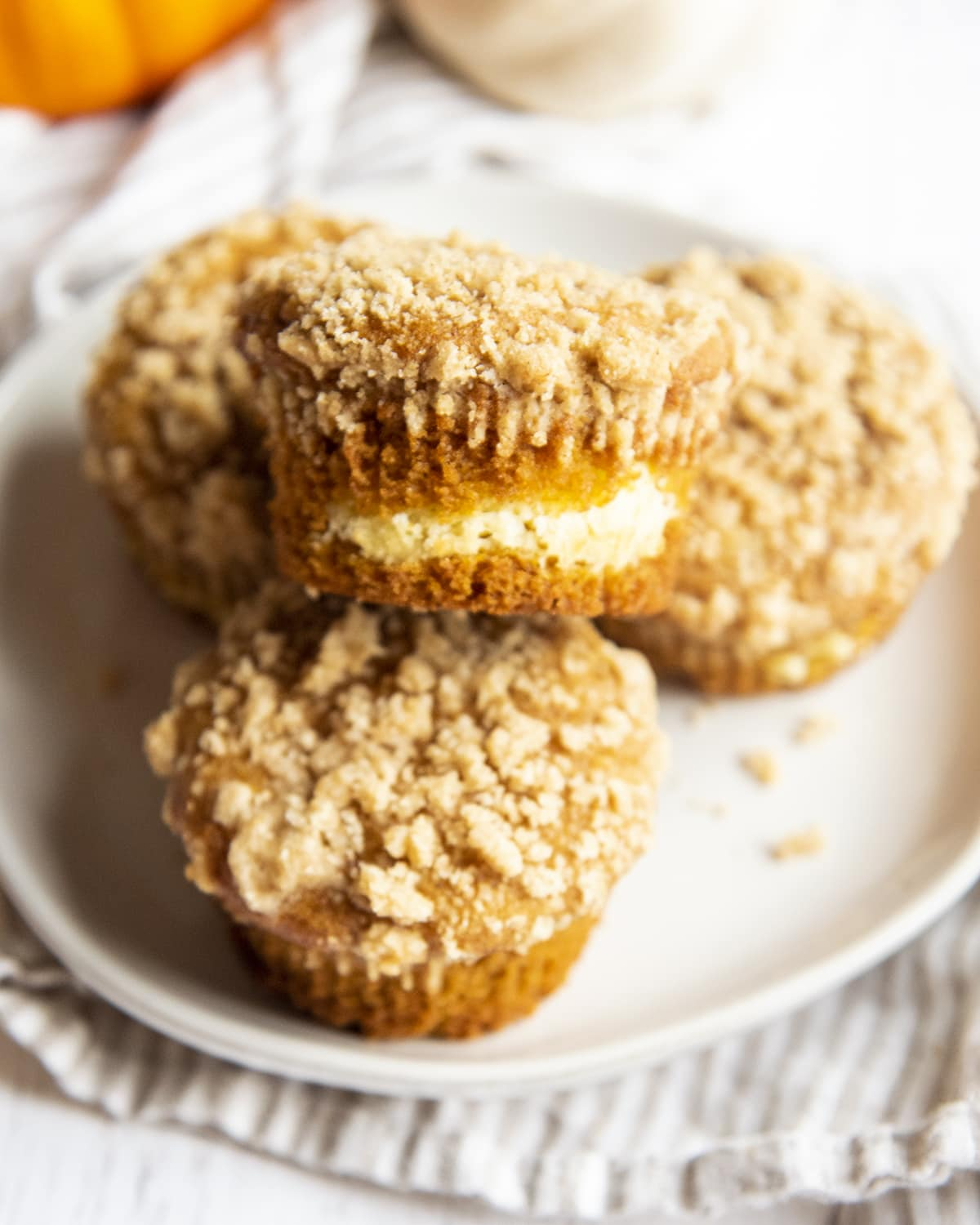 A pile of pumpkin cheesecake muffins on a small plate.