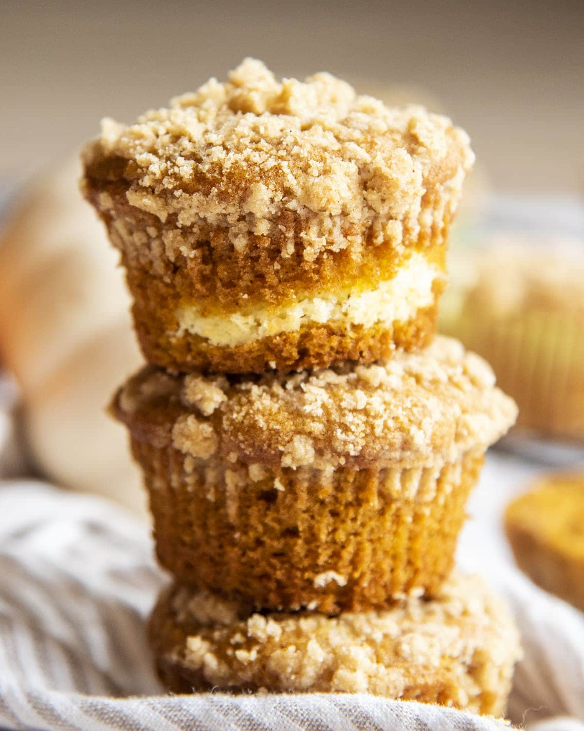 A stack of 3 pumpkin cream cheese muffins with a streusel crumb on top.
