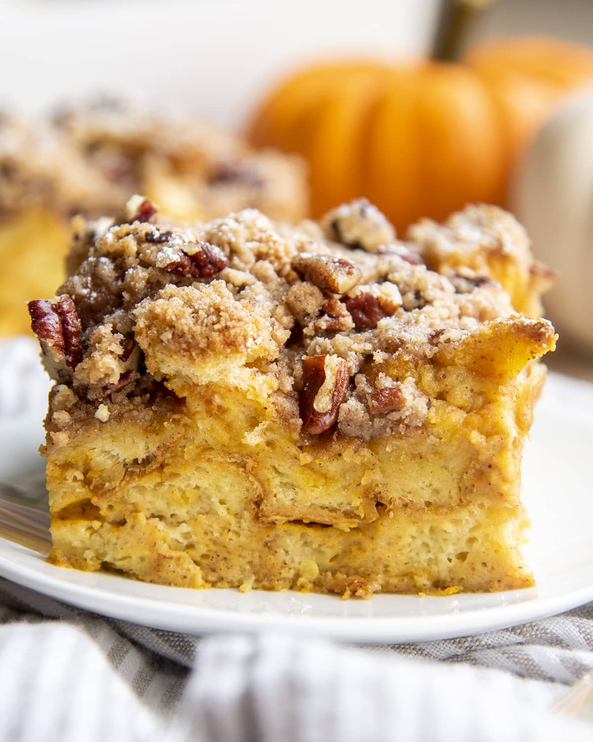 A piece of french toast casserole topped with a pecan cinnamon streusel topping.