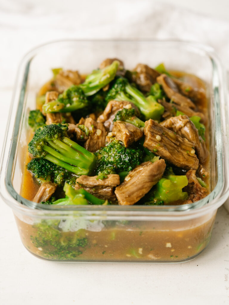 Three quarter view of easy beef and broccoli in a glass container