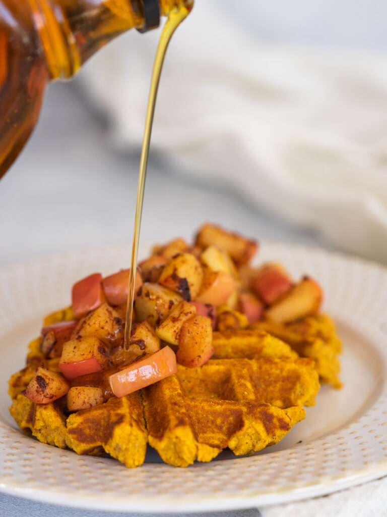 maple syrup pouring onto pumpkin spice waffles with cinnamon apples
