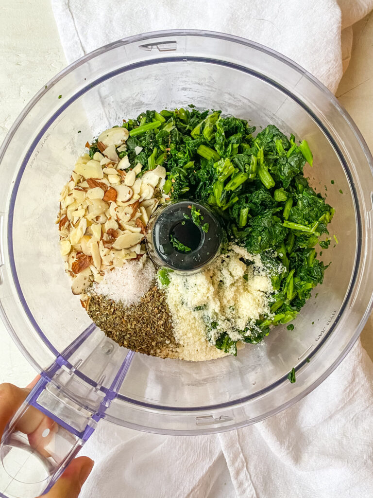 Ingredients for a budget friendly kale pesto in a food processor