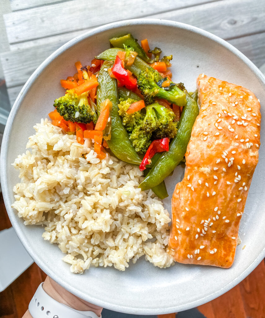 above view sheet pan salmon meal on a plate with veggies and rice