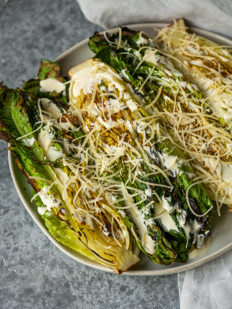 Three quarter view of grilled caesar salad with homemade caesar dressing and parmesan cheese