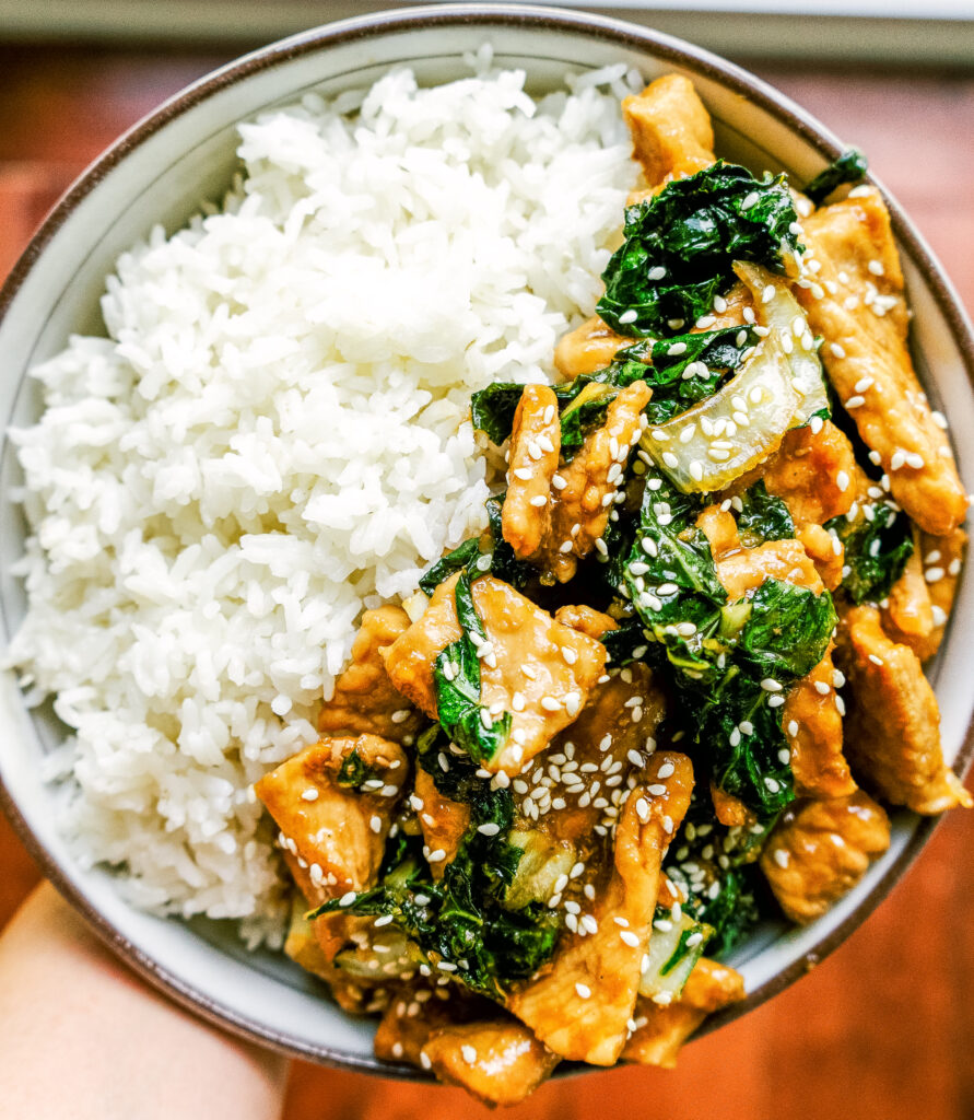 Above view of teriyaki pork and bok choy in a bowl with white rice