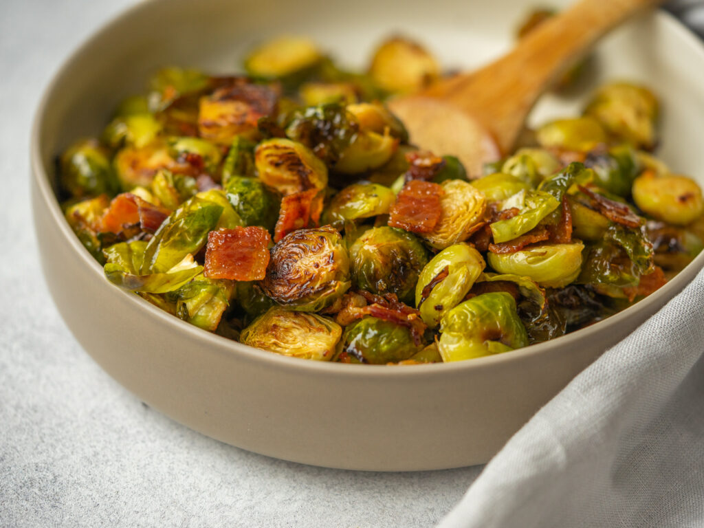Three quarter view of maple bacon brussels sprouts in a serving bowl