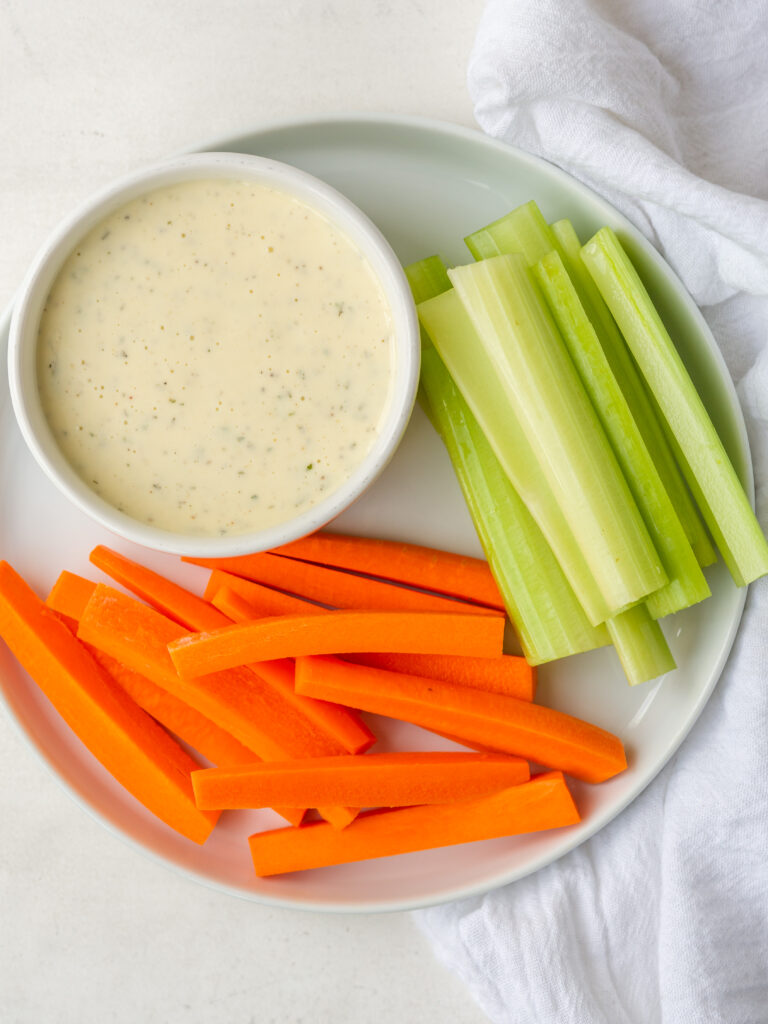 Above view of Homemade Ranch Dressing in a small bowl on a plate with raw cut veggies
