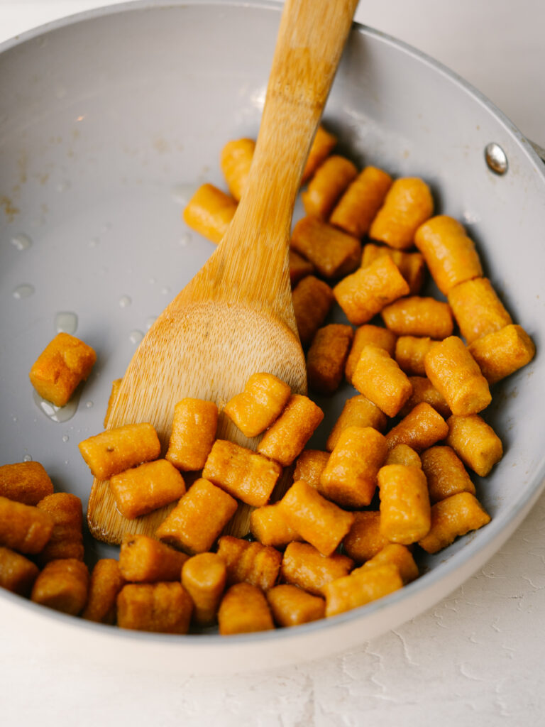 overhead view of sweet potato gnocchi in a pan with a spoon