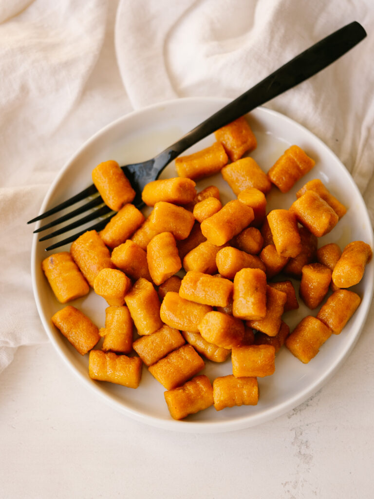 above view of cooked sweet potato gnocchi on a plate with a fork