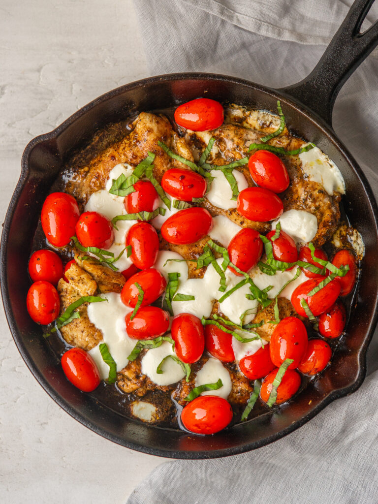 Above view of balsamic caprese chicken in a cast iron skillet