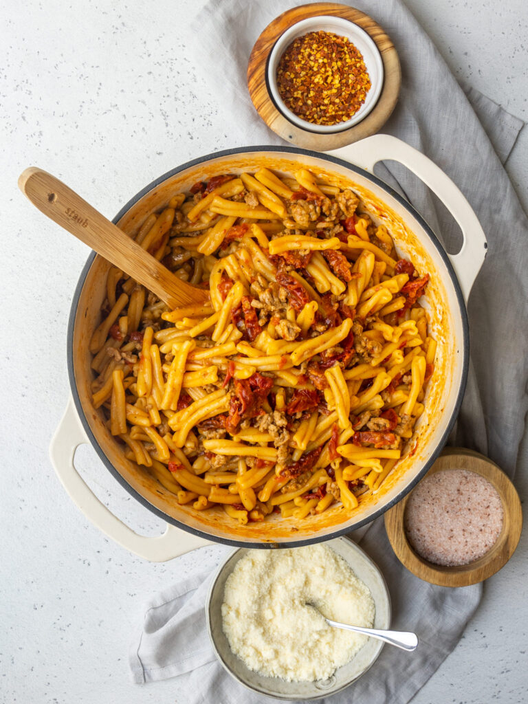 above view of a pot of sun dried tomato pasta in a large pot with a spoon in it