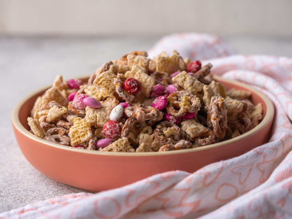 Side view of strawberry valentine's snack mix in a pink serving bowl