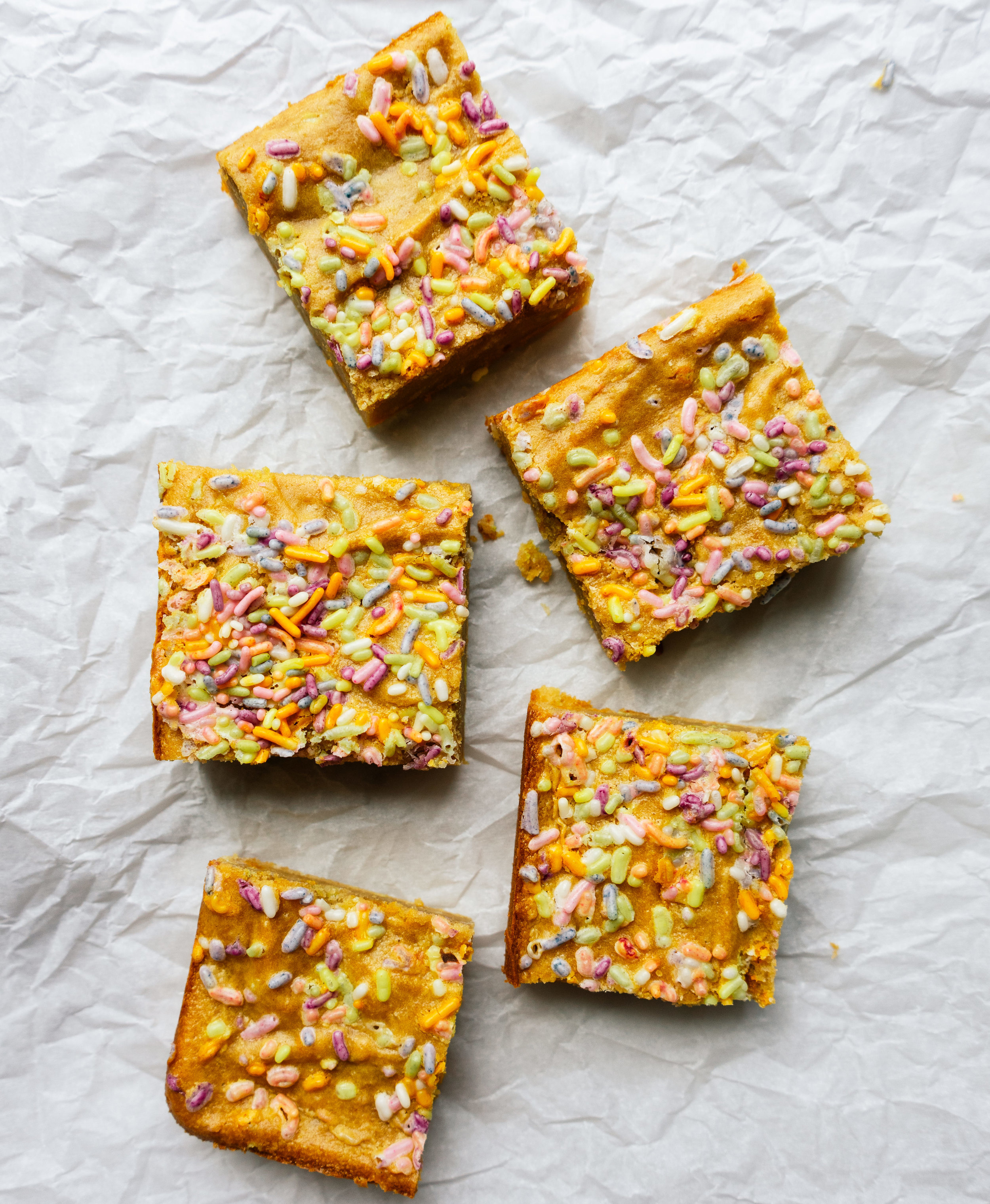 Above view of cake batter blondies on a sheet of parchment